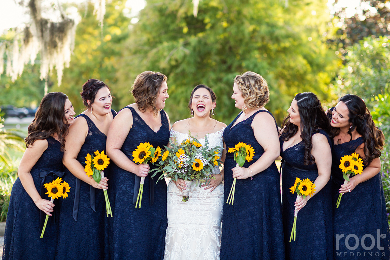 A bride laughing with bridesmaids in navy dresses with sunflower bouquets