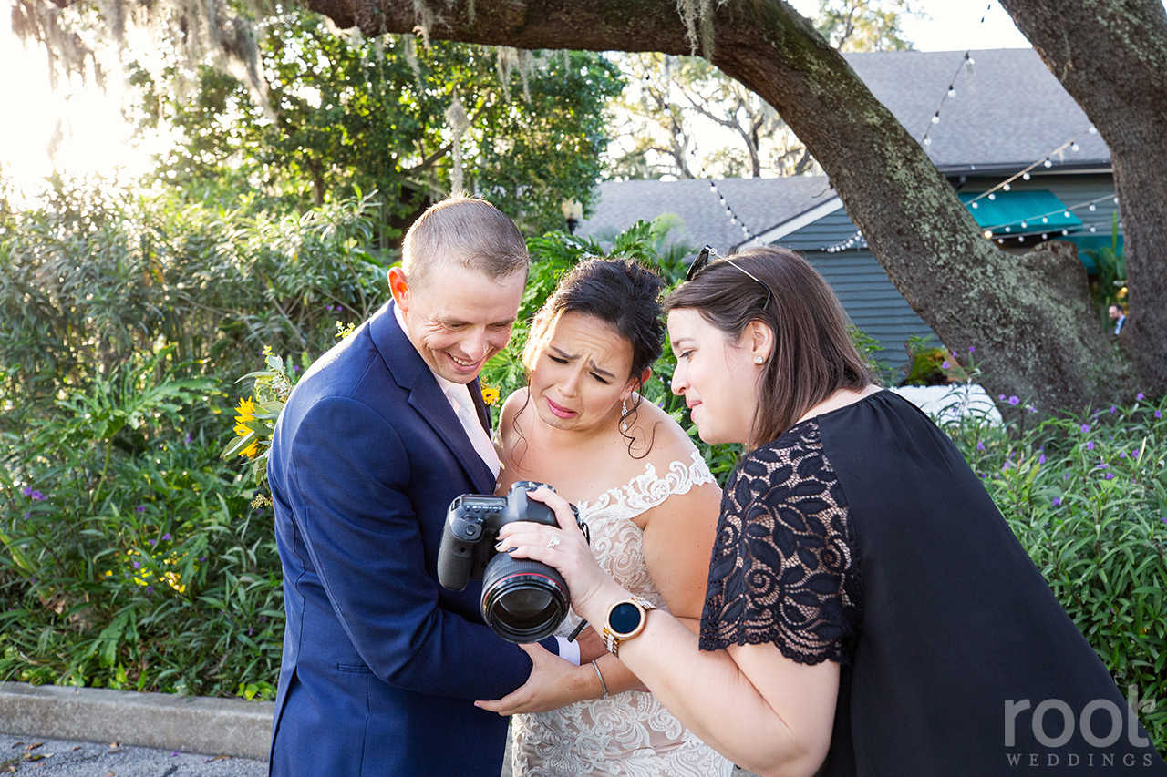 Jensey Root shows a bride and groom a photo