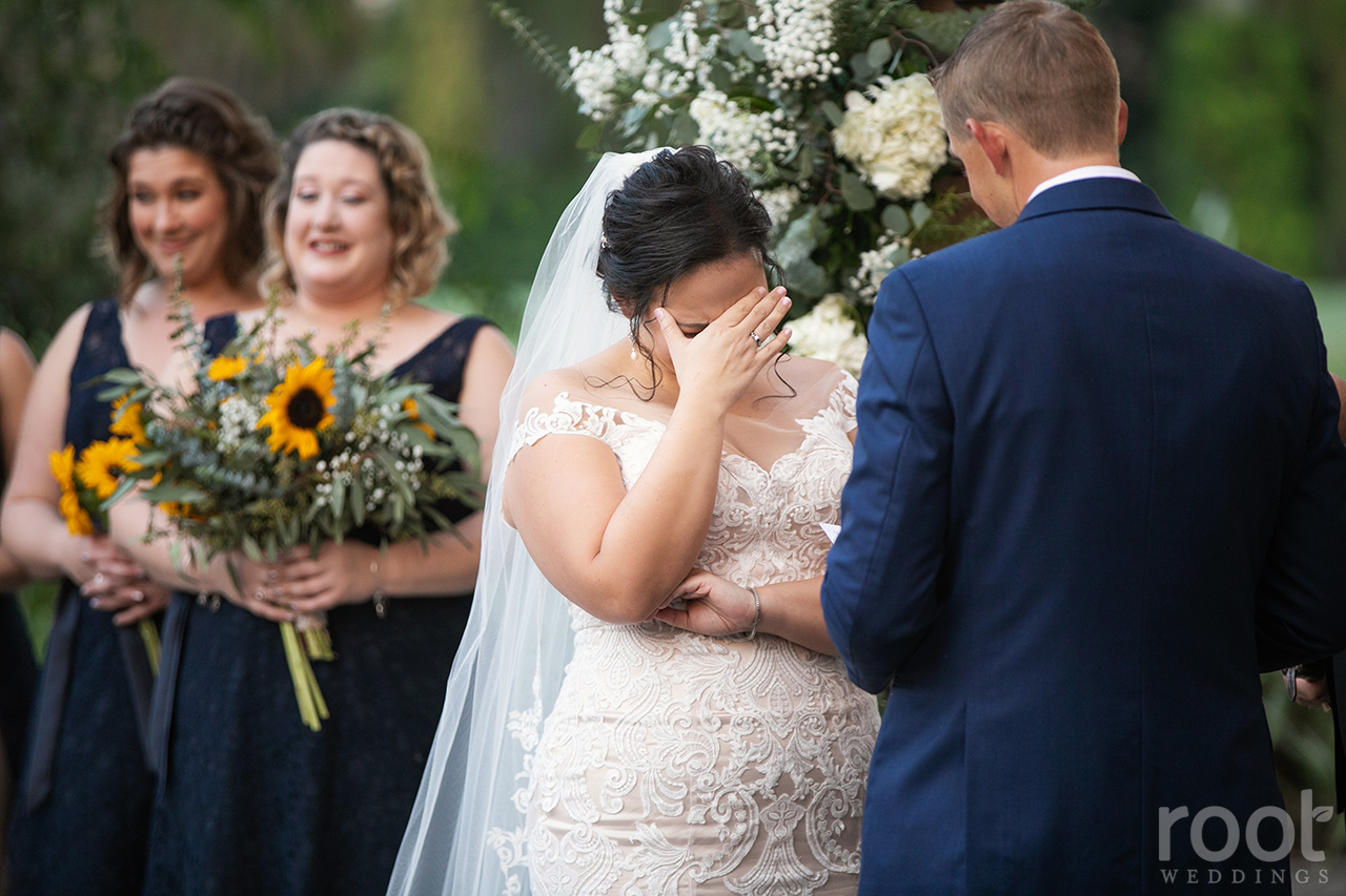 Bride covers her face crying during wedding vows