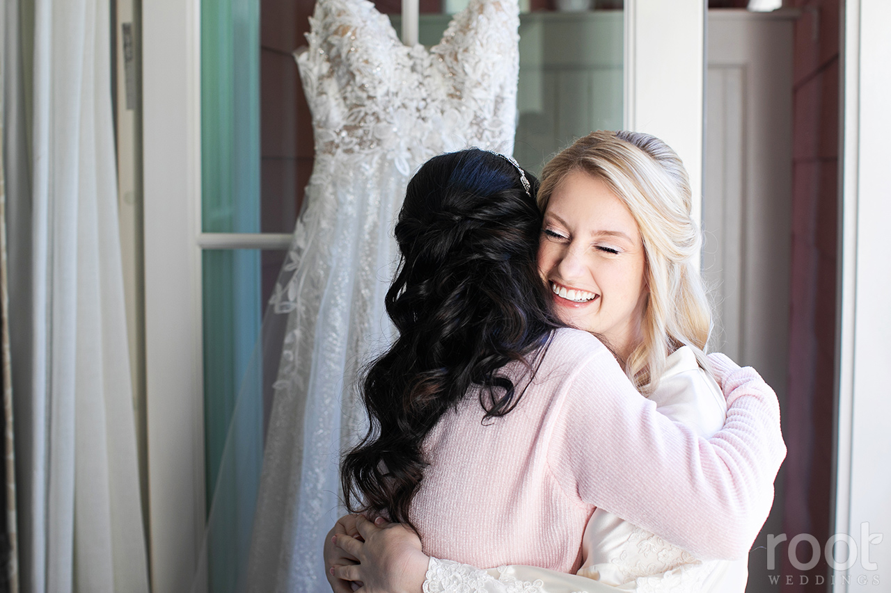 Mother of the bride hug in front of a wedding dress