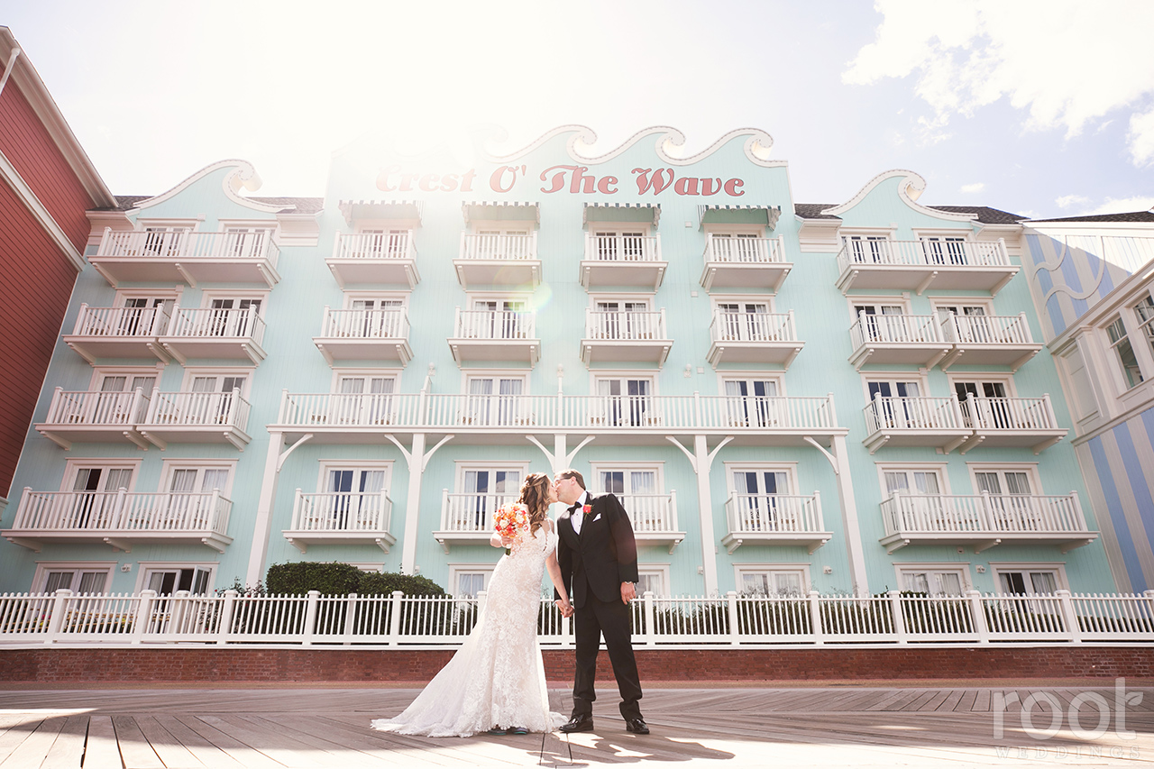 Bride and groom kissing at Disney's Boardwalk Inn Crest of the Wave Building