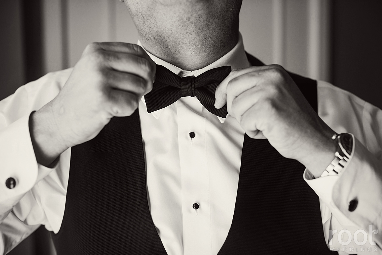 Groom straightening his bowtie